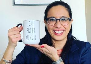 """Me smiling and holding up a mug that says, """"Dr. Priya Kumar."""""""